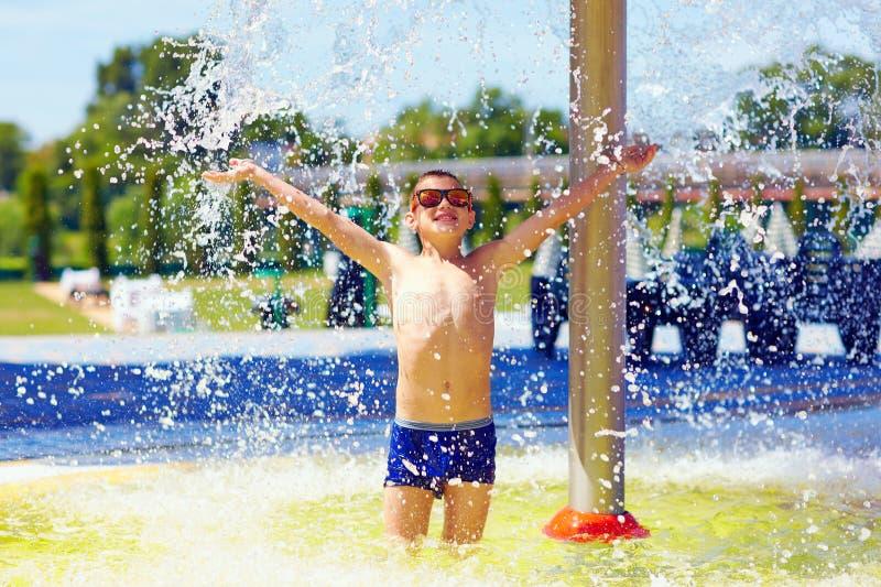 Opgewekte jongen die van de zomer genieten onder de waterstroom stock foto's