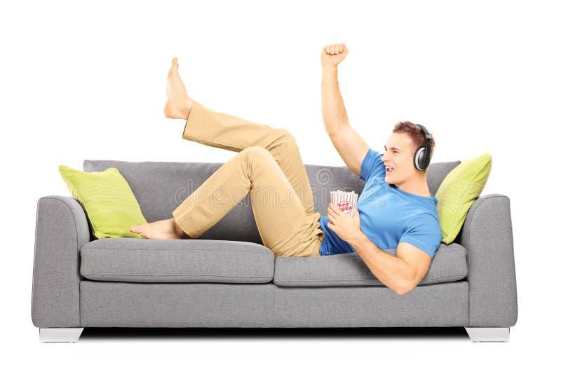 Opgewekte kerel die op een bank en het luisteren muziek liggen royalty-vrije stock afbeelding