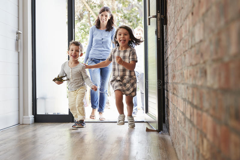Opgewekte Kinderen die naar huis met Ouders aankomen royalty-vrije stock afbeelding