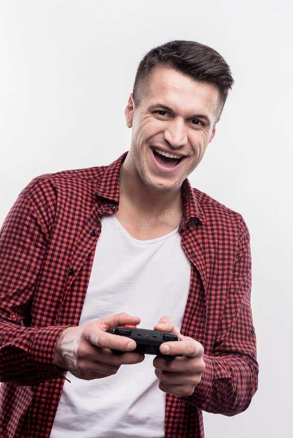 Opgewekte knappe mens die gelukkige het spelen videospelletjes voelen royalty-vrije stock afbeelding