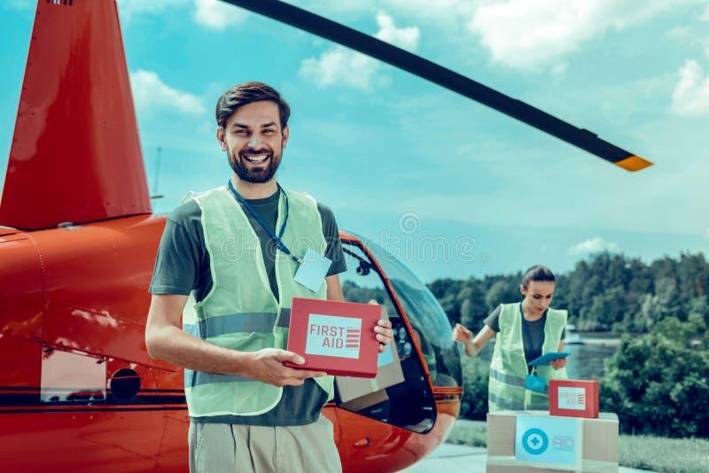 Opgewekte kortharige kerel die als vrijwilliger werken en eerste hulpdoos houden stock foto