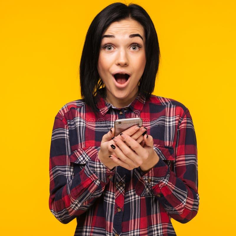 Opgewekte lachende vrouw in plaidoverhemd die en mobiele telefoon over gele achtergrond bevinden zich met behulp van royalty-vrije stock afbeelding