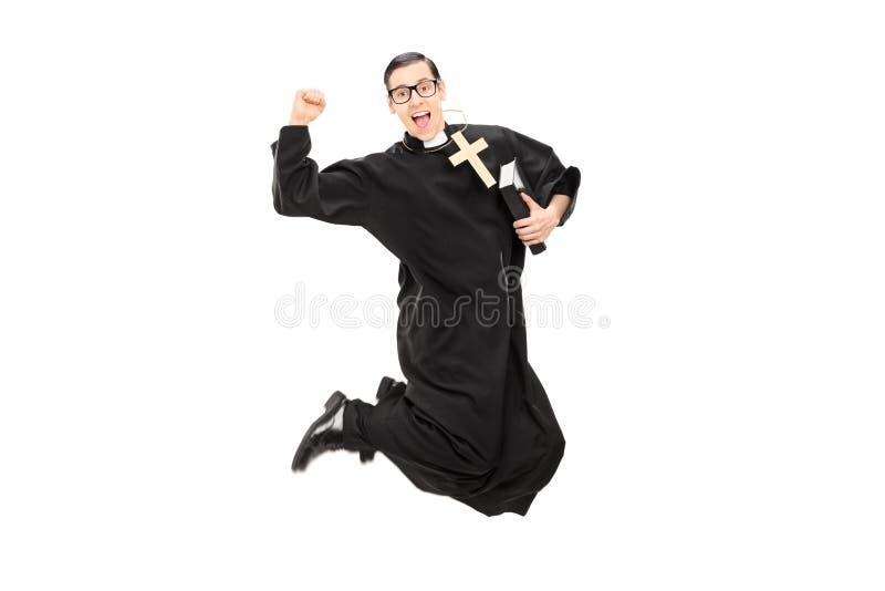 Opgewekte mannelijke priester die met vreugde springen stock afbeeldingen