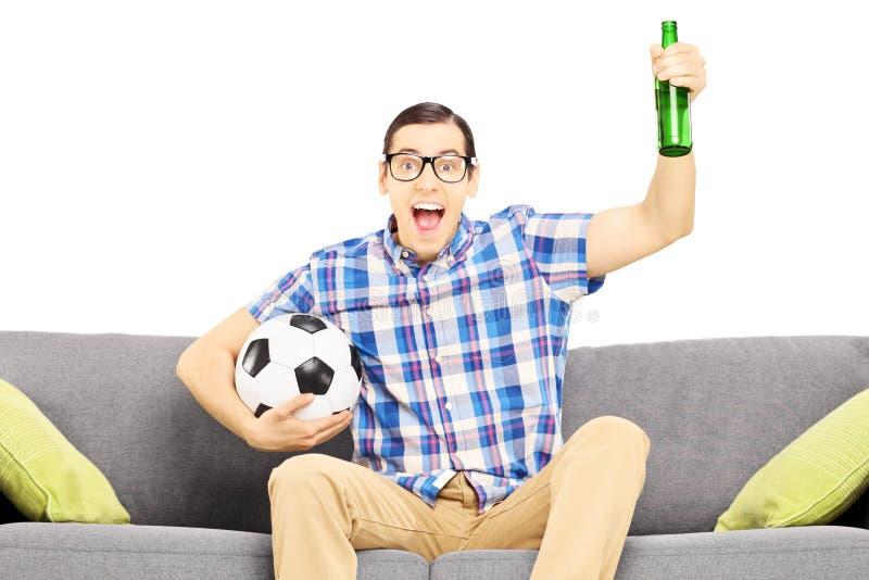 Opgewekte mannelijke sportventilator met voetbalbal en bier het letten op sport stock foto's
