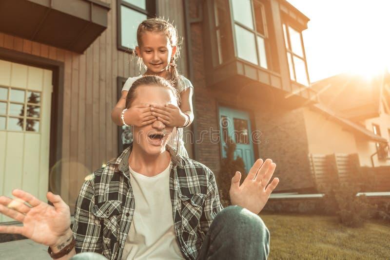 Opgewekte meisje sluitende ogen van haar expressieve vader stock foto