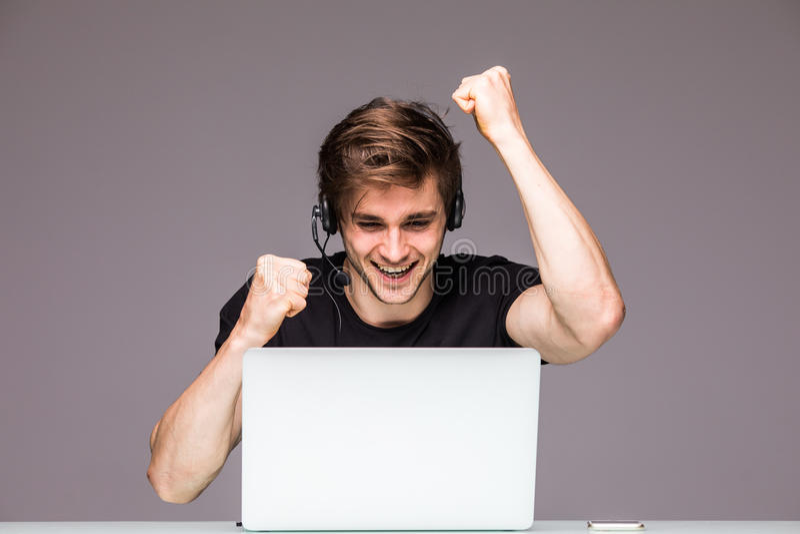 Opgewekte mens die een overwinning op laptop spel joying Gokkenconcept royalty-vrije stock fotografie