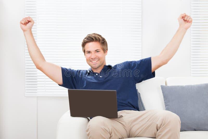 Opgewekte mens die met laptop handen opheffen stock foto's