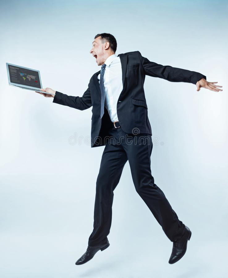 Opgewekte mens die van zaken met laptop over achtergrond springen royalty-vrije stock foto
