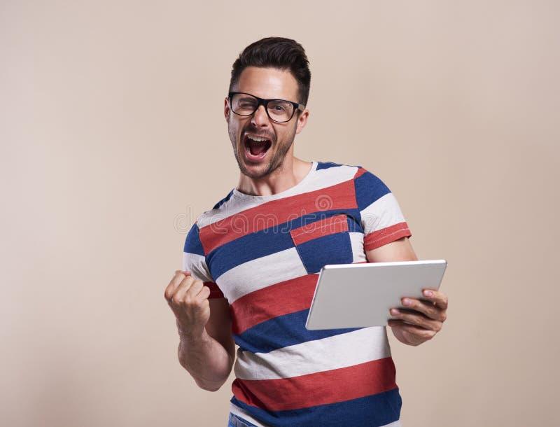 Opgewekte mens met tablet in studioschot royalty-vrije stock afbeelding