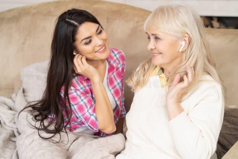 Opgewekte moeder en dochter die earpods aan muziek gebruiken te luisteren royalty-vrije stock foto