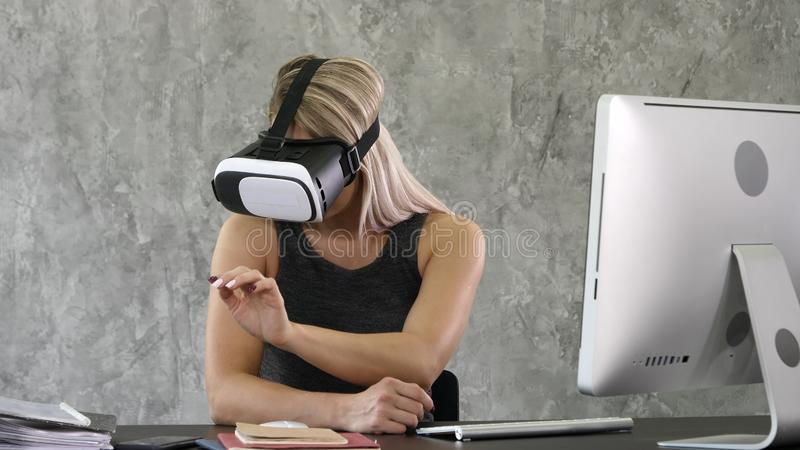 Opgewekte onderneemster die virtuele werkelijkheidsglazen, gelukkige vrouw dragen die vergrote wereld onderzoeken, die met digita stock afbeelding