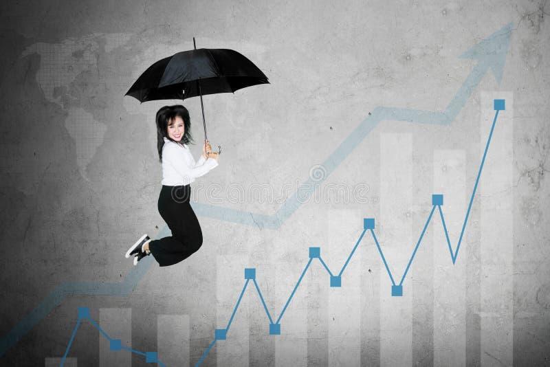 Opgewekte onderneemstersprongen met de groeigrafiek stock afbeeldingen