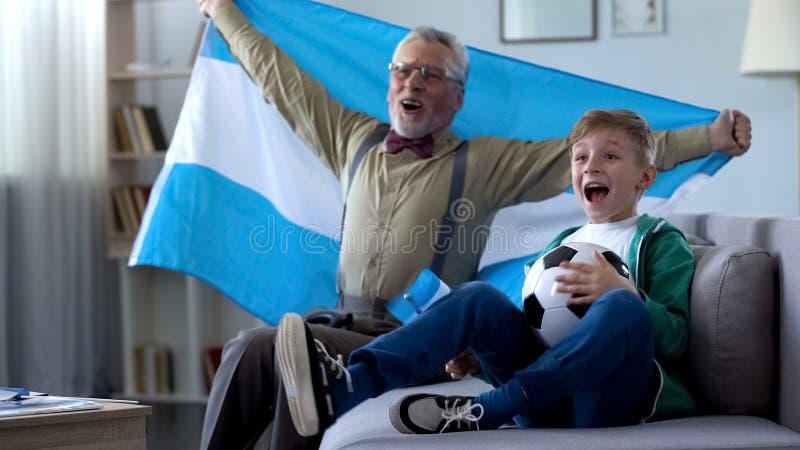 Opgewekte oude mens en weinig jongen het vieren overwinning van de voetbalteam van Argentinië stock afbeeldingen