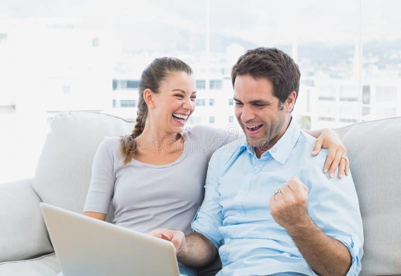 Opgewekte paarzitting op de bank die laptop samen met behulp van royalty-vrije stock afbeeldingen