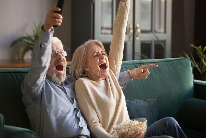 Opgewekte rijpe paar, man en vrouwen het letten op voetbal, het vieren overwinning stock afbeeldingen
