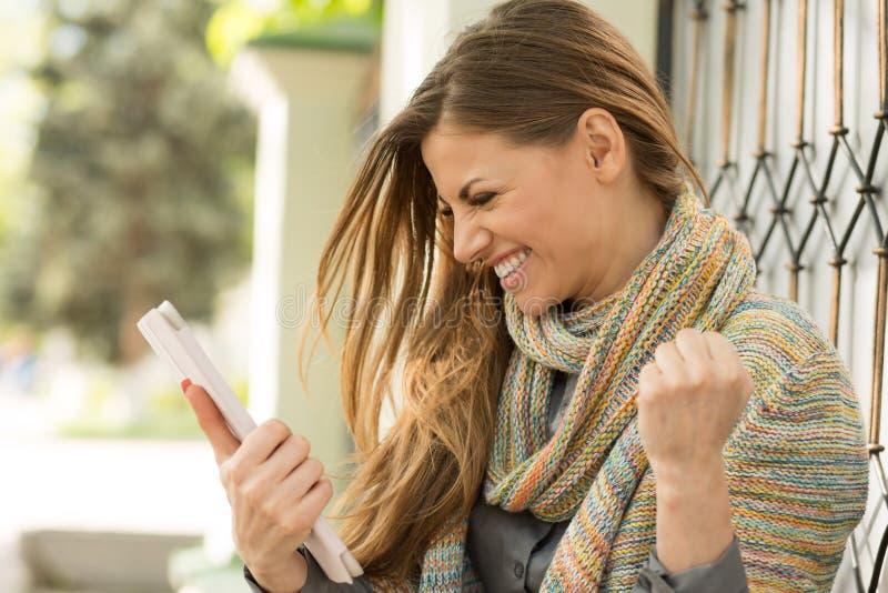 Opgewekte student die goed nieuws online op een tabletcomputer lezen in de straat op een de zomerdag stock fotografie
