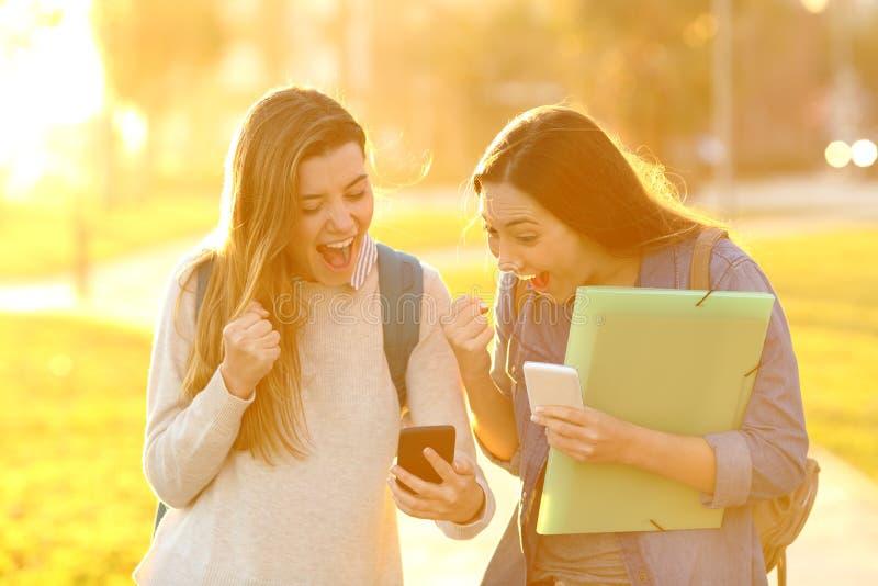 Opgewekte studenten die goed nieuws vinden bij zonsondergang online royalty-vrije stock afbeelding