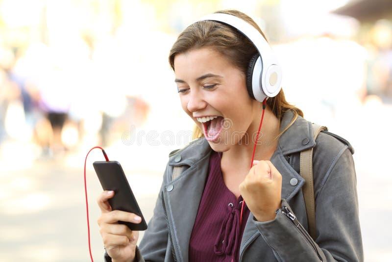 Opgewekte tiener het luisteren muziek op een telefoon stock foto