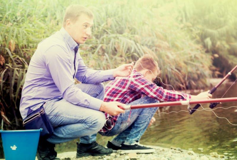Opgewekte volwassen mens die op zoetwatermeer op bos vissen royalty-vrije stock afbeeldingen
