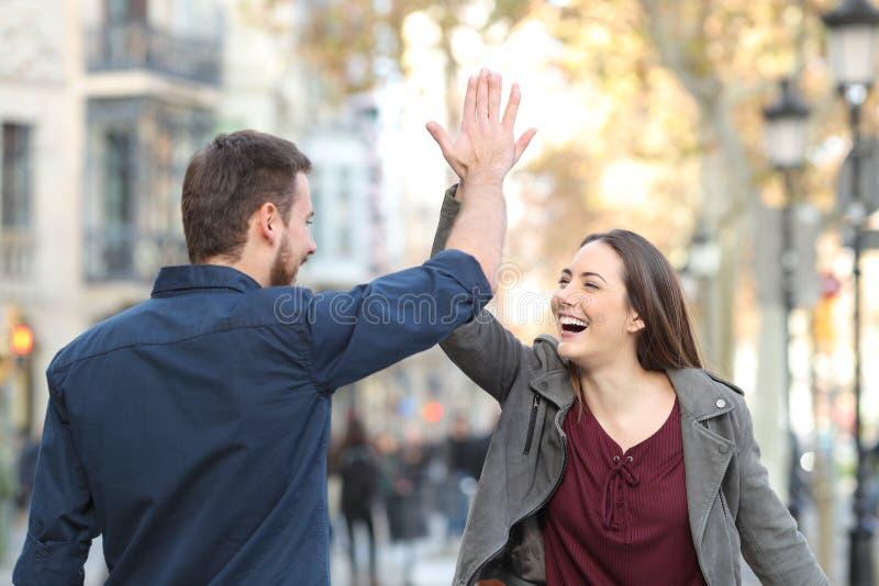 Opgewekte vrienden die hoogte vijf in de straat geven royalty-vrije stock foto's