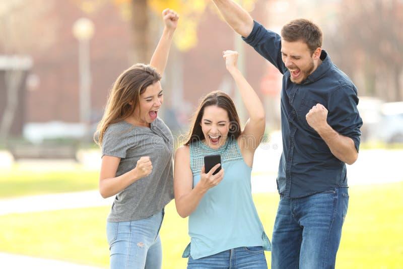 3 opgewekte vrienden die lezings goede netw op telefoon springen royalty-vrije stock foto