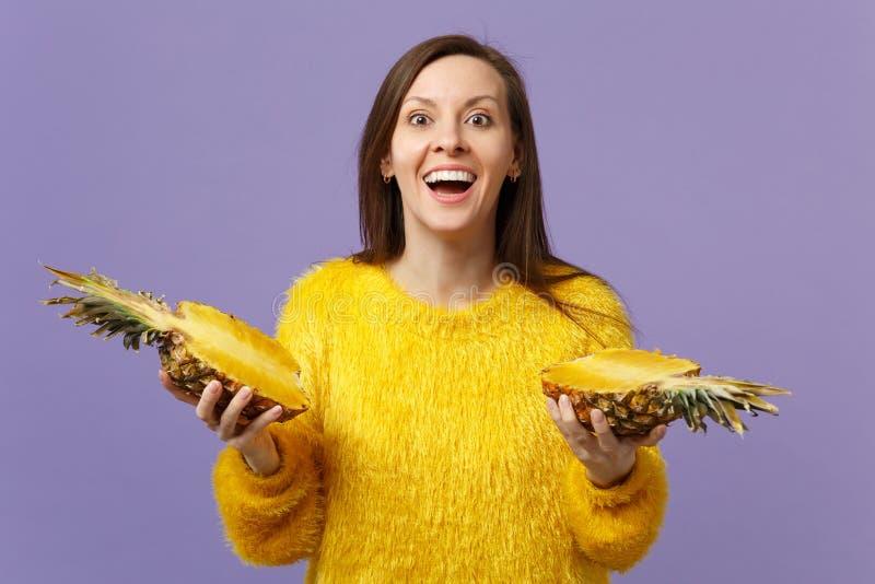 Opgewekte vrolijke jonge vrouw die in bontsweater in hand halfs van vers rijp die ananasfruit houden op viooltje wordt geïsoleerd stock afbeelding