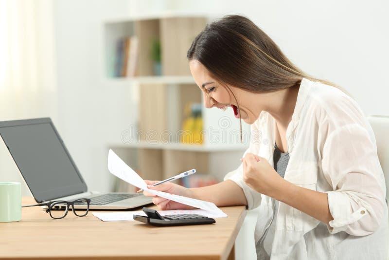 Opgewekte vrouw die bankafschrift controleren stock afbeeldingen