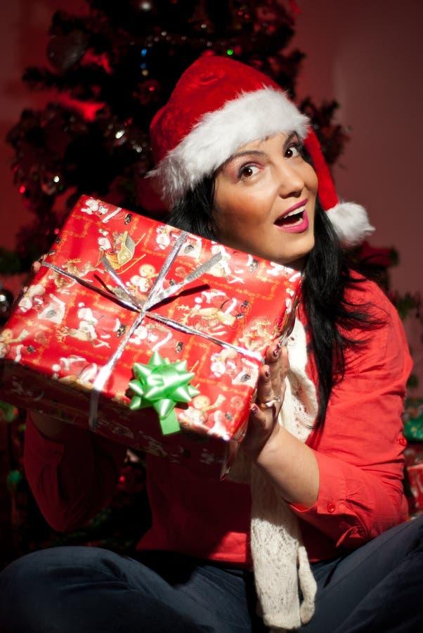 Opgewekte vrouw die haar aanwezige Kerstmis opheft royalty-vrije stock foto