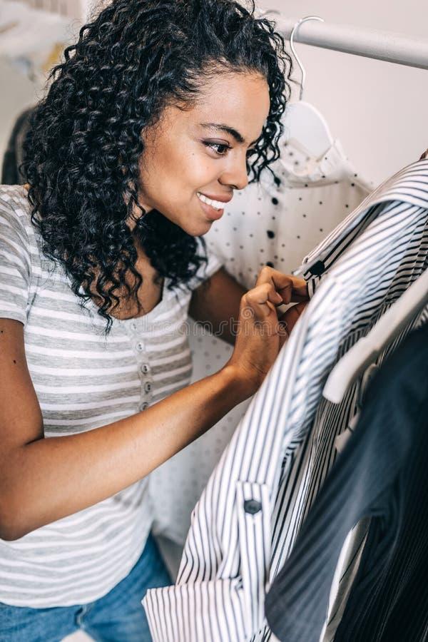 Opgewekte vrouw die kleren in winkel onderzoeken royalty-vrije stock afbeeldingen