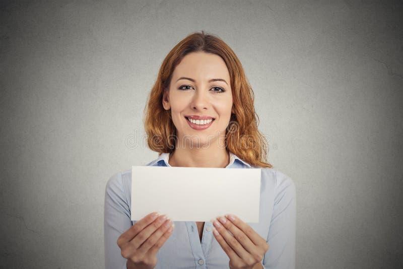 Opgewekte vrouw die leeg leeg document kaartteken met exemplaarruimte tonen royalty-vrije stock foto