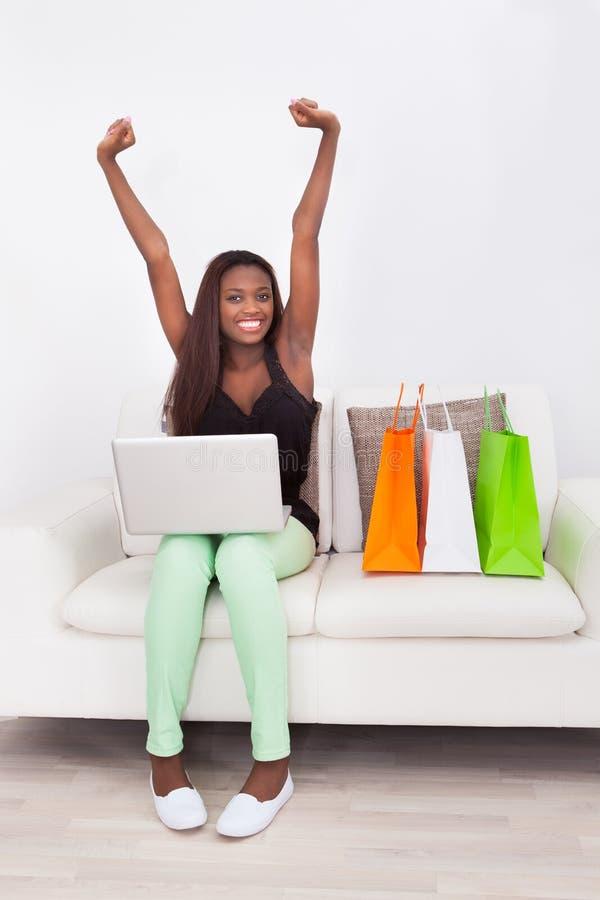 Opgewekte Vrouw die online thuis winkelen royalty-vrije stock afbeeldingen