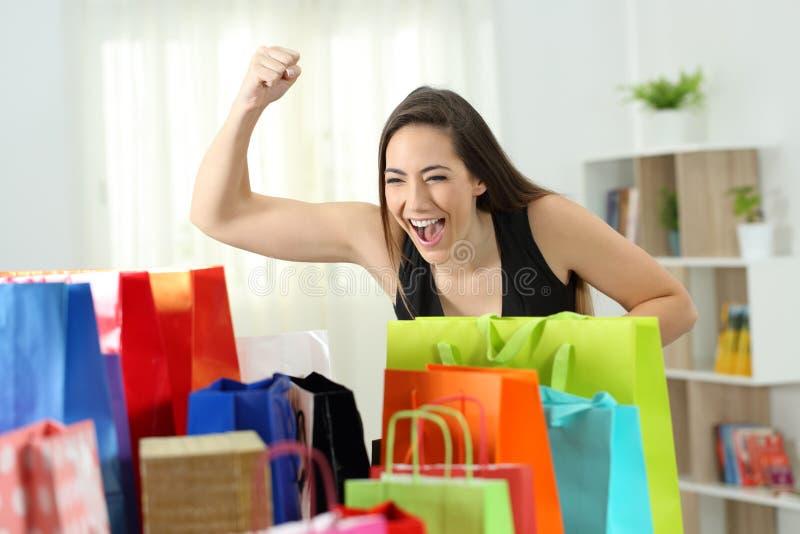 Opgewekte vrouw die veelvoudige het winkelen zakken bekijken stock foto's