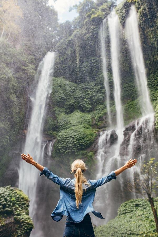 Opgewekte vrouw die zich door waterval bevinden stock afbeelding