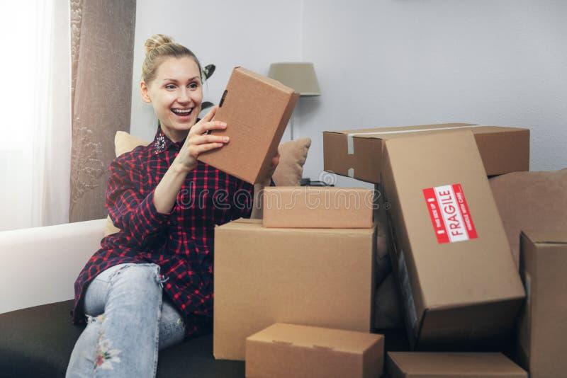 Opgewekte vrouw het openen dozen na thuisbezorging royalty-vrije stock foto