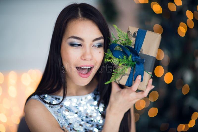 Opgewekte vrouw in Kerstnachtzitting dichtbij boom en het opheffen van haar Kerstmisgift om welke ` s binnen te luisteren royalty-vrije stock afbeeldingen