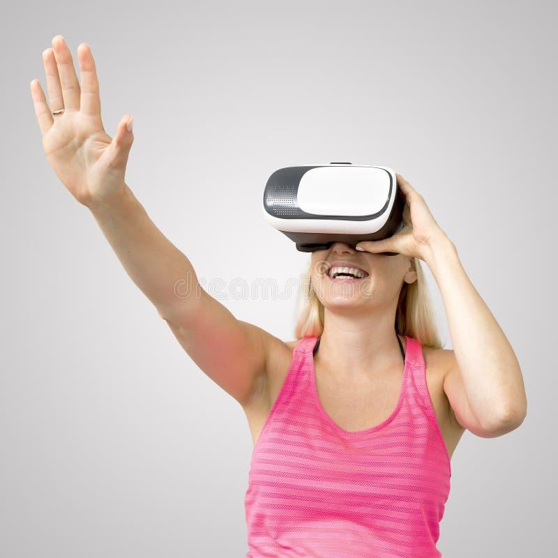 Opgewekte vrouw met virtuele werkelijkheidsglazen op grijs stock afbeelding