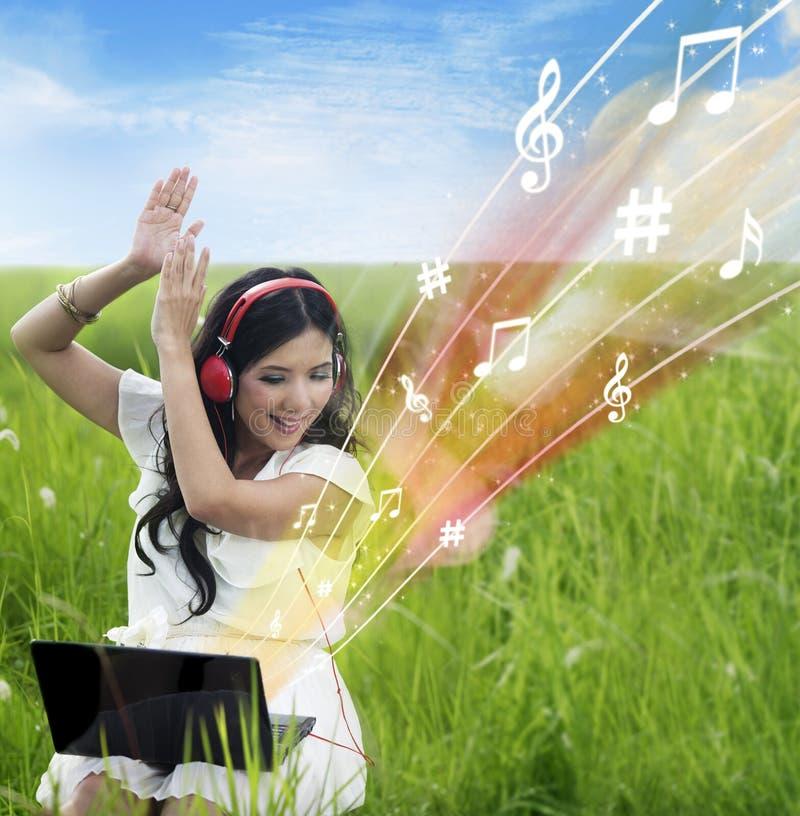 Opgewekte Vrouwelijke Downloadmuziek Van Openlucht Laptop - Stock Afbeeldingen