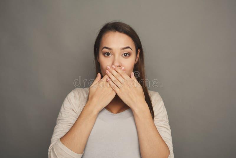 Opgewekte zwangere vrouw die haar mond sluiten royalty-vrije stock afbeelding