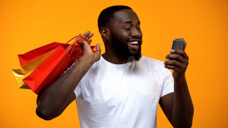 Opgewekte zwarte mannelijke holding het winkelen zak en smartphone, de contant geld achterdiensten royalty-vrije stock foto