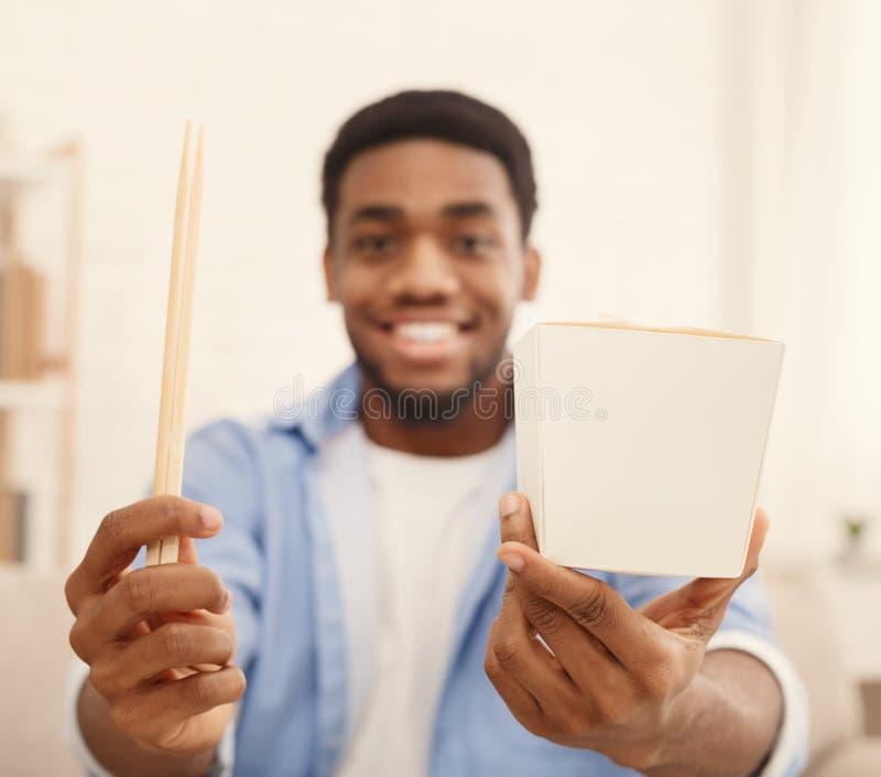 Opgewekte zwarte mens die leveringsdoos en eetstokjes tonen royalty-vrije stock foto