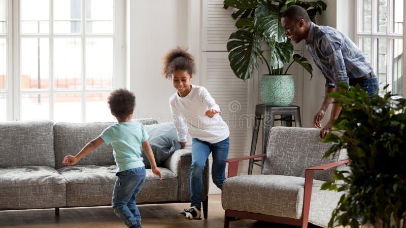 Opgewekte zwarte papa die grappig spel met kinderen thuis spelen royalty-vrije stock afbeeldingen