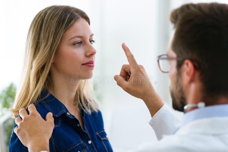 Ophtalmologiste masculin attrayant de docteur vérifiant la vision d'oeil de la belle jeune femme dans la clinique moderne photo stock