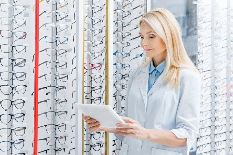 ophtalmologue féminin professionnel à l'aide du comprimé numérique dans l'optique avec des verres photos libres de droits