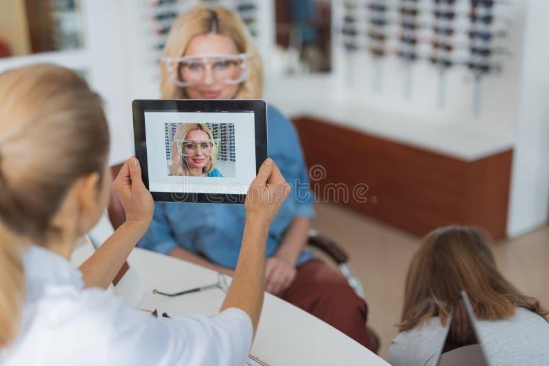 Ophthalmiologist professionnel utilisant des technologies modernes pour la correction de vue images stock