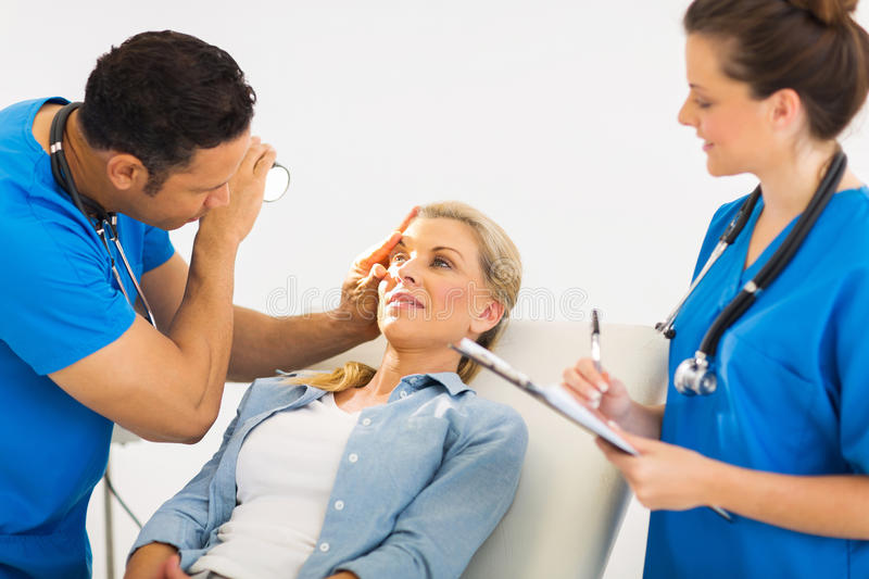 Ophthalmologist examining woman. Friendly ophthalmologist examining woman's eye stock photo