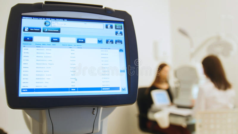 Ophthalmologist in eyes clinic doing diagnostic with vision of patient by modern computer systems - high technology. Health care, close up stock photography