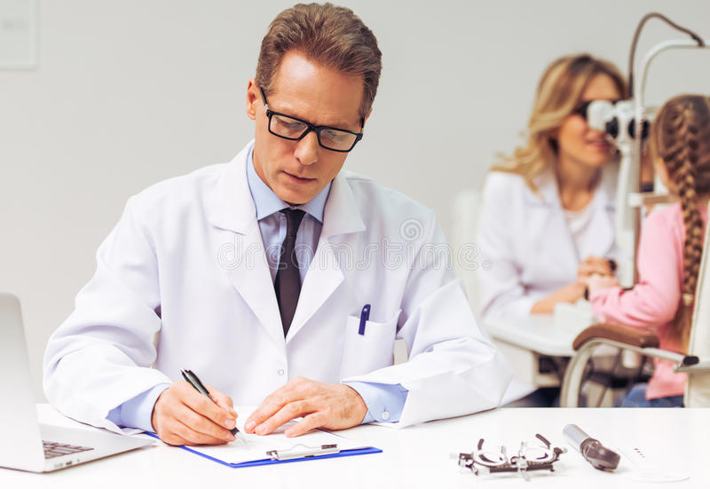 At the ophthalmologist. Handsome ophthalmologist making notes, in the background female ophthalmologist examining little girl stock photography