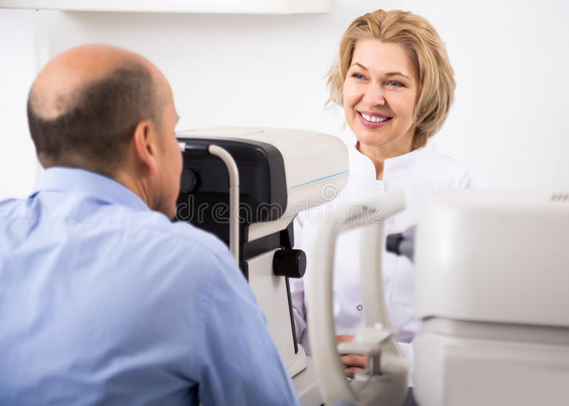 Ophthalmologist and male pensioner checking eyesight royalty free stock image