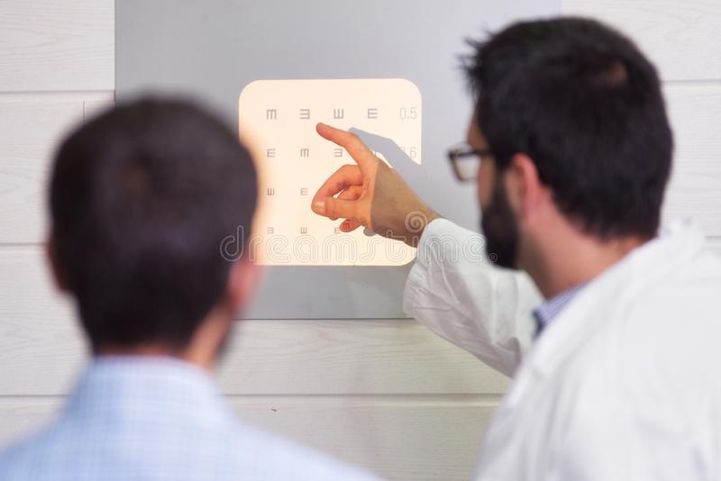 Ophthalmologist pointing at letters while patient is reading the eye chart. Ophthalmologist pointing at letters while patient is reading the eye chart royalty free stock photo