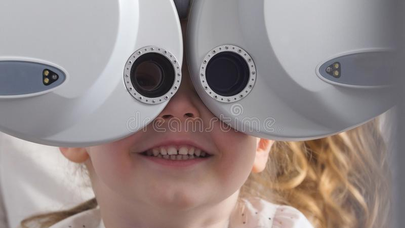 Ophthalmology clinic - smiling little blonde girl checks vision eyesight, close up. Telephoto royalty free stock image